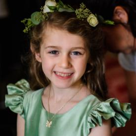 A flower girl wearing a sage green pure silk flower girl dress with butterfly sleeves and a green hair wreath.