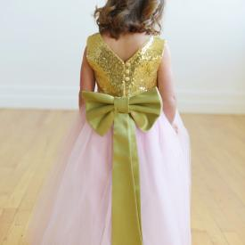 A young junior bridesmaid wearing a gold sequin flower girl dress with a sequin bodice and a blush pink tulle skirt. The dress has a big green bow.
