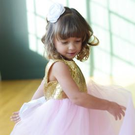 A young junior bridesmaid wearing a gold sequin flower girl dress with a sequin bodice and a blush pink tulle skirt. The dress has a big white bow.