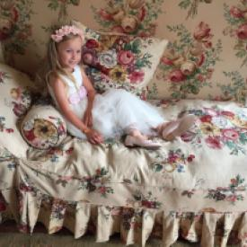 a flower girl or junior bridesmaid sitting on a floral chair wearing a pink and ivory flower girl dress.