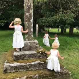 A group of toddler flower girls at a wedding wearing cotton flower girl dresses in ivory and white.