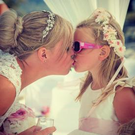 A bride kissing a flower girl who is wearing an ivory flower girl dress with a blush pink sahs which ties in a big bow,