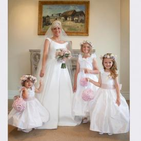 A bride in an ivory wedding dress and a group of flower girls wearing a silk flower girl dress in ivory.