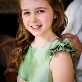 A flower girl at a wedding wearing a sage green flower girl dress in pure silk.