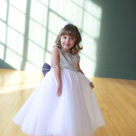 A young junior bridesmaid wearing a flower girl dress with a white sequin bodice and a white tulle skirt and a big purple bow.