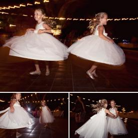 Flower girls spinning and dancing on a stage wearing ivory flower girl dresses with tulle skirts and roses.