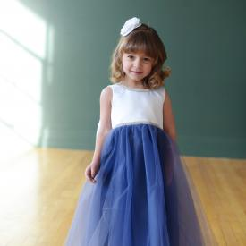 A toddler flower girl at a wedding wearing a flower girl dress with a blue tulle skirt and a white duchess satin bodice with diamante trim.