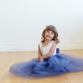 A toddler junior bridesmaid at a wedding wearing a flower girl dress with a blue tulle skirt and a white duchess satin bodice with diamante trim.