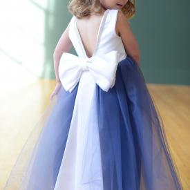 A flower girl at a wedding wearing a flower girl dress with a blue tulle skirt and a white duchess satin bodice with diamante trim.