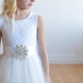 A young girl wearing a lace and tulle flower girl dress with a diamante ribbon sash. These dresses are handmade in London, UK.
