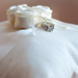 A wedding ring pillow with three flowers and a ribbon holding the wedding rings