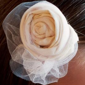 A girl wearing a cream cotton hair clip for flower girls and junior bridesmaids with tulle on a barette hair clip