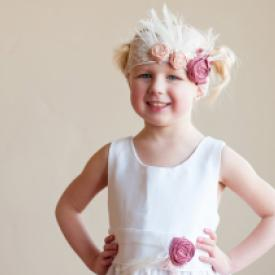 A five year old girl wearing a boho style flower girl dress in white with pink flowers. The  girl also has an elasticated flower girl headband with dusky pink flowers on it.