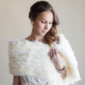 A bride wearing an ivory feathered wedding shawl over her wedding dress.