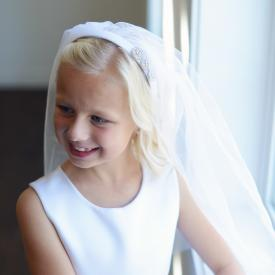 A girl wearing a made to measure white hand made first communion veil with diamanté