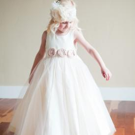 A three year old girl at a wedding wearing a designer ivory cotton flower girl dress or junior bridesmaid dress with a tulle overlay and blush pink flowers on the sash.