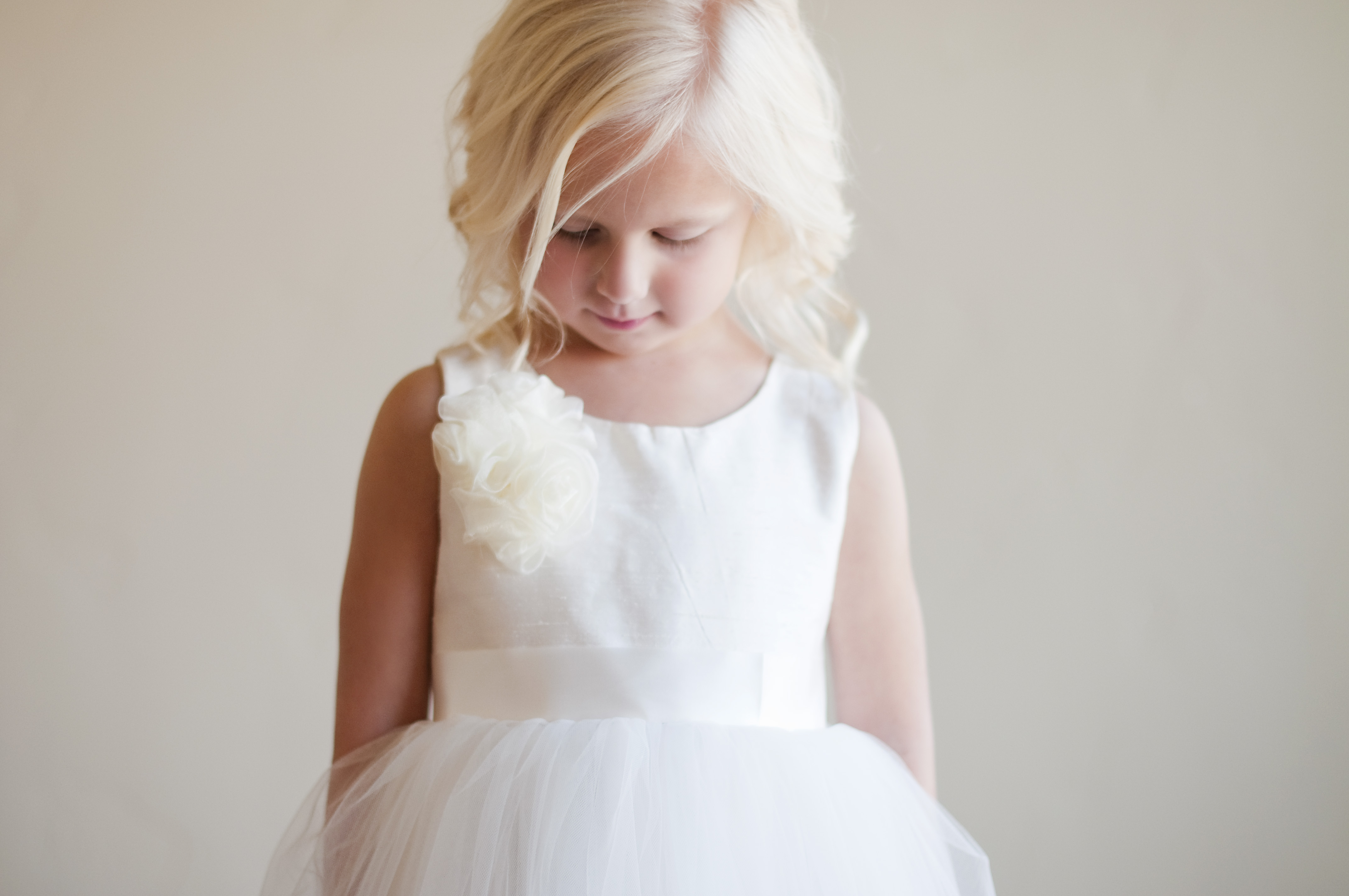 e5b8951acd6 An ivory or white first communion and flower girl dress in silk and tulle  with a peony style flower embellishment.